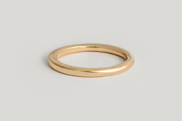 A close up of a yellow gold band that is rounded on one end and transitions to be squared on the other