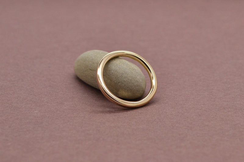 A yellow gold band that is rounded on one end and transitions to be squared on the other leaned against a small grey stone ontop of a blush colored surface