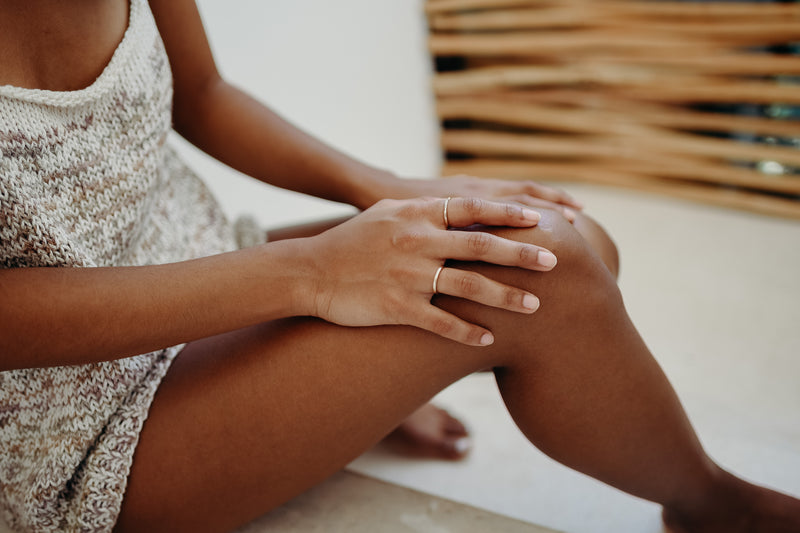 A person wearing a neutral toned knit slip dress with their hand resting on their knee modeling the Enzo band on their pointer finger and the Ageku yellow gold band on their ring finger