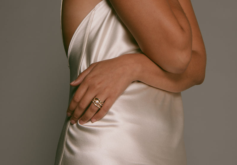 M. Hisae bridal set - two Lana Bands and a Crown Theia Ring - on a model in cream silk dress.