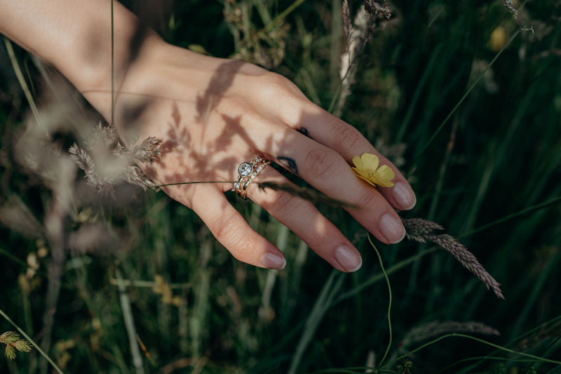 A hand in a grassy field modeling the white diamond crown kaori and white diamond enzo band stacked together on the ring finger. The hand is lightly grabbing a small yellow flower.