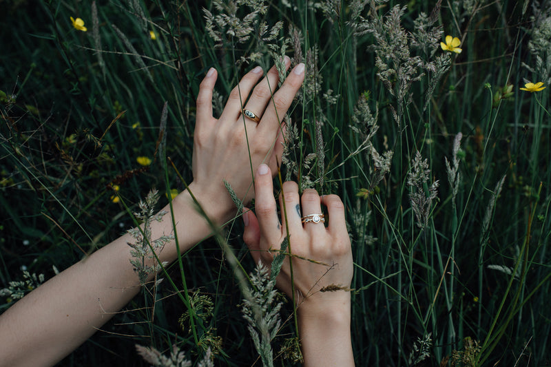 Two hands against a tall grassy field. The righ thand is modeling the whit diamond enzo band and white diamond crown kaori on the ring finger while the left hand has the green sapphire classic risa ring on the middle finger.