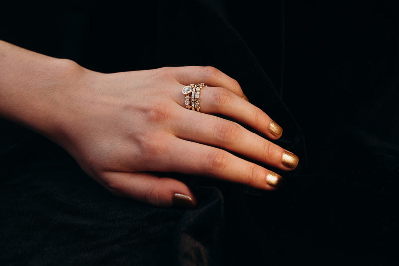 A hand with gold nail polish on resting against a black velvet back drop is modeling a stack of yellow gold rings featuring the white diamond crown kaori trinity ring, the white diamond enzo band and the 5 stone koemi ring on the ring finger.