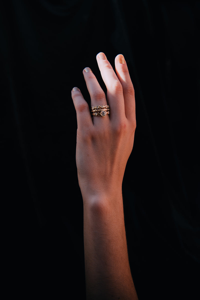 A hand with gold nail polish on reaching up against a black velvet back drop is modeling a stack of yellow gold rings featuring the white diamond crown kaori trinity ring, the white diamond enzo band and the 5 stone koemi ring on the ring finger.