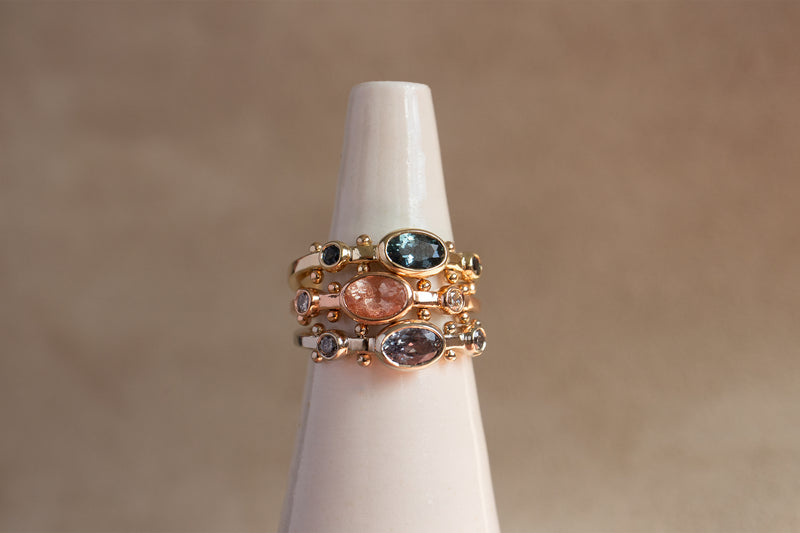 A close up view of a ring stack featuring the dark teal sapphire Kaori ring in yellow gold, the rose gold sunstone oval Kaori, and a clear quartz Kaori in 14k white gold against a tan background.