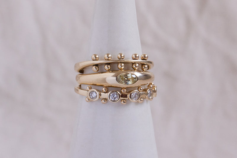 A close up view of a yellow gold ring stack featuring the Maya band, the yellow sapphire petite ring, and 5-stone white diamond Koemi rings against a tan background