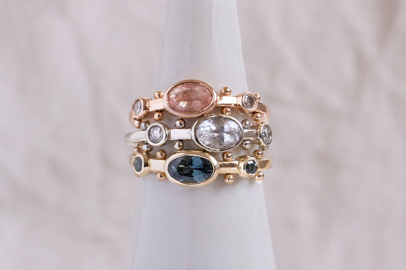 A closeup of a stack featuring the Clear Quartz Oval KaoriI Ring, the Suntstone Oval Kaori ring and the Dark Teal Sapphire Kaori ring against a white background.