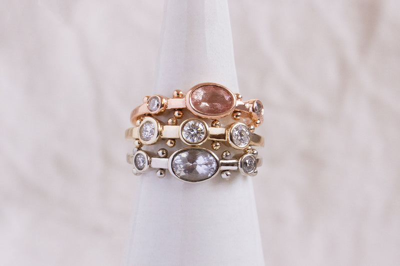 A close up view of a ring stack featuring the dark teal sapphire Kaori ring in yellow gold, the rose gold sunstone oval Kaori, and a clear quartz Kaori in 14k white gold against a white background.