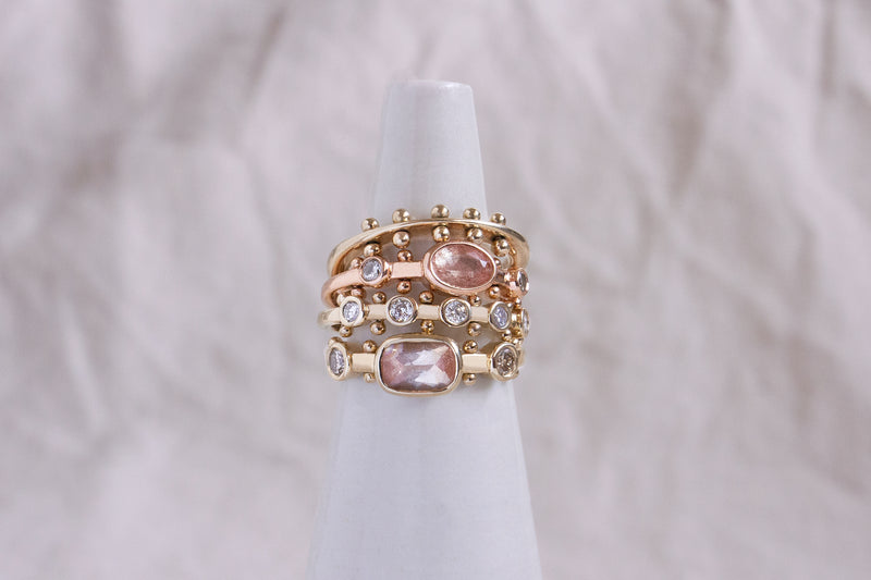 A stack including the yellow gold Maya ring, the rose gold oval Kaori ring, and the five stone yellow gold Koemi ring