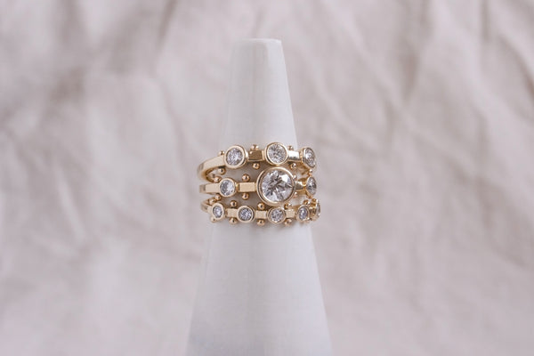 A close up view of a ring stack featuring the 3-stone, Crown Kaori, and 5-stone white diamond Koemi rings all with gold balls between each diamond setting along the sides of the band against a white background.