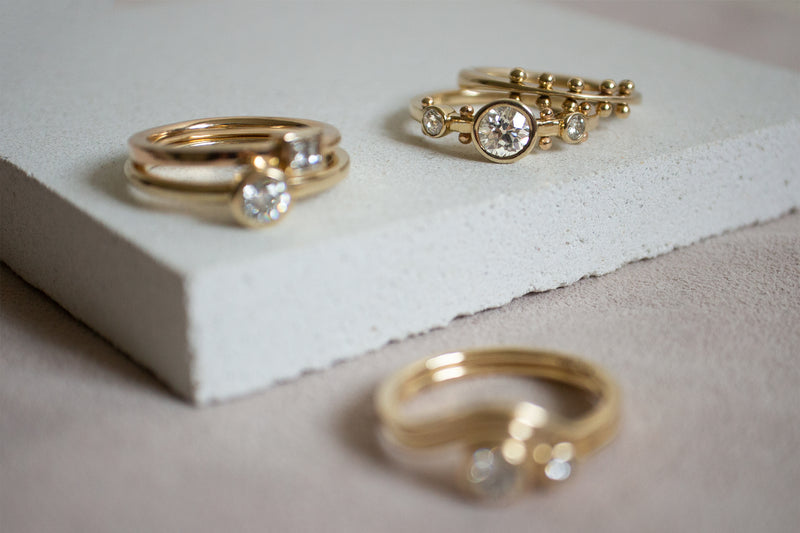 A style shot of five M. Hisae gold rings on their sides on a white stone block. The white diamond masumi is blurry and out of focus in the front. A stack featuring two solitaire diamond bands is on the left and the white diamond crown Maori and maya ring are stacked on the right.