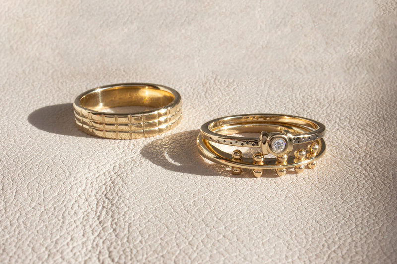 Three yellow gold bands on their sides on top of beige lather featuring the shoji band, white gold catori, and the maya ring.