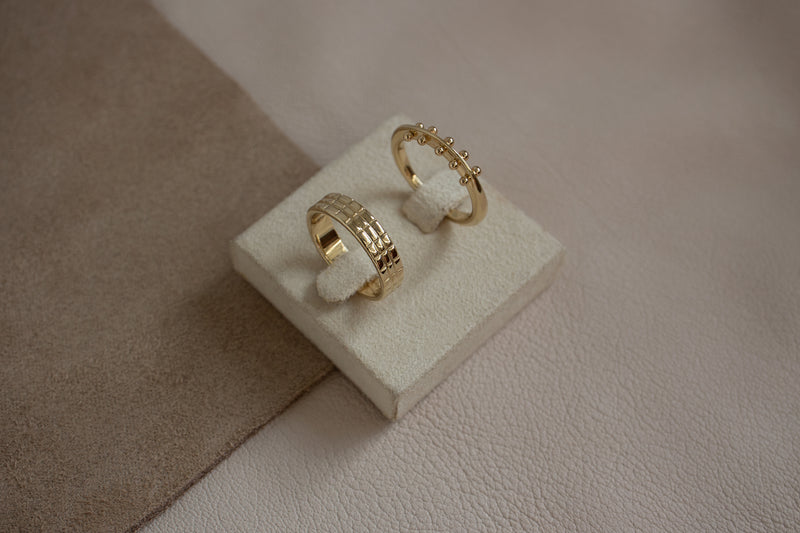 A top view of the maya ring and shoji band standing up on a small white display box against an off white leather textured surface.