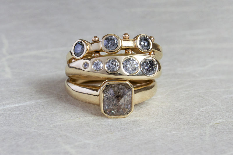 A stack of grey diamond yellow gold rings featuring the Koemi, Lila Sumprima and Takara rings