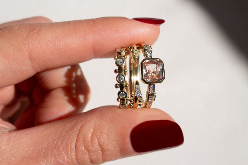 Two fingers holding a stack of three rings. 1) 5-Stone Koemi Ring with five white diamonds in bezel settings and bead detailing in between each bezel. 2) Kuli Ring, an open band with white diamonds set into the points and bead detailing just beyond the diamonds. 3) Hikaru Ring No.1 with an emerald cut light pink sapphire, white diamond carre/square cut diamonds, and white round diamonds flush set into the band.