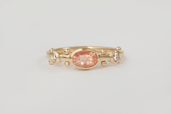 A yellow gold band with two small white diamond settings and large oval sunstone set in the middle. The band has a total of four sets of gold balls between each diamond setting along the sides of the band.