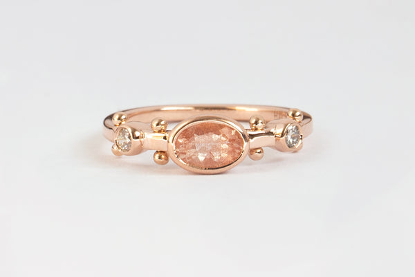 A front view of a rose gold band with two small white diamond settings and large oval sunstone set in the middle. The band has a total of four sets of rose gold balls between each diamond setting along the sides of the band.