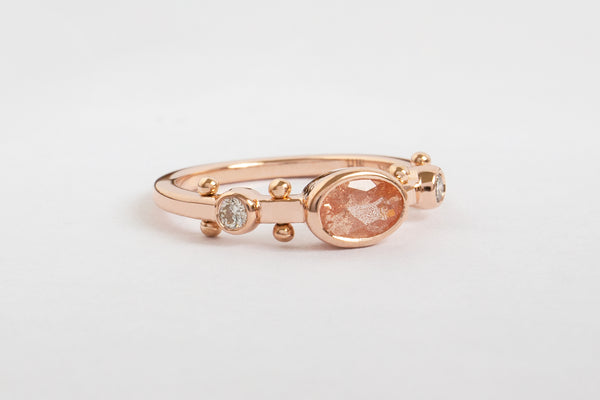 A side view of a rose gold band with two small white diamond settings and large oval sunstone set in the middle. The band has a total of four sets of rose gold balls between each diamond setting along the sides of the band.