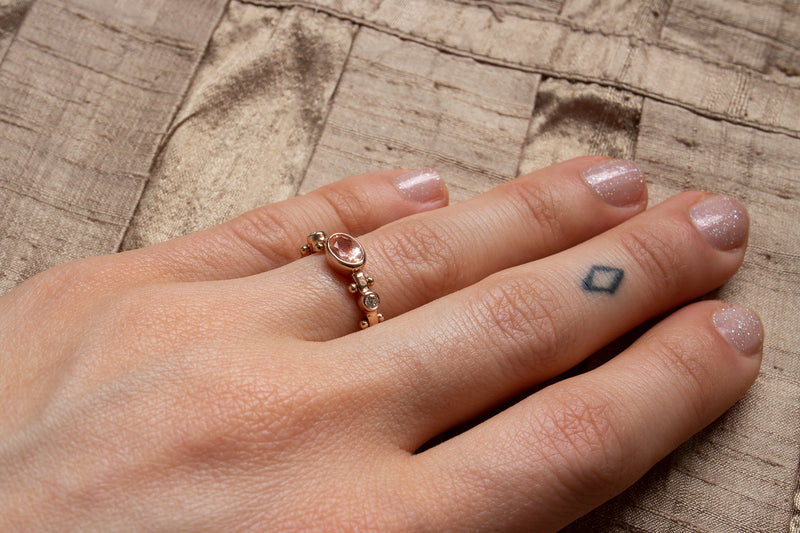 A left hand with nude sparkly nail polish wearing the sunstone Kaori ring on the ring finger against a taupe silk fabric