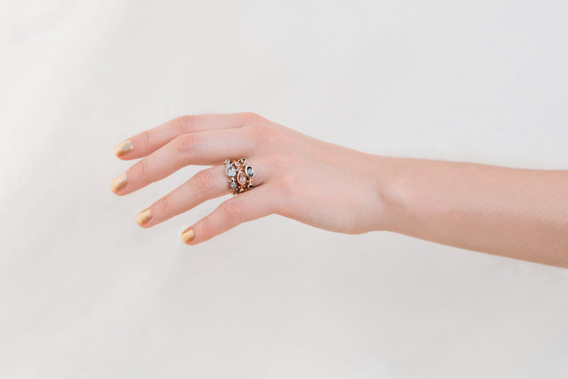 A hand with sheer gold nail polish modeling the Clear Quartz Oval KaoriI Ring, the Suntstone Oval Kaori ring and the Dark Teal Sapphire Kaori ring all on the left ring finger reaching sideways against a white background