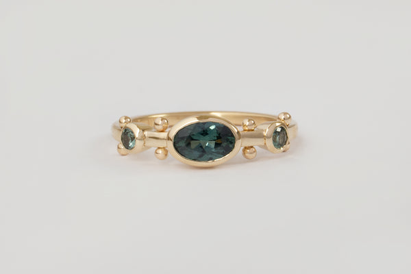 A yellow gold band with two small circular teal saphire settingss and large oval teal sapphire set in the middle. The band has a total of four sets of gold beads between each diamond setting along the sides of the band.