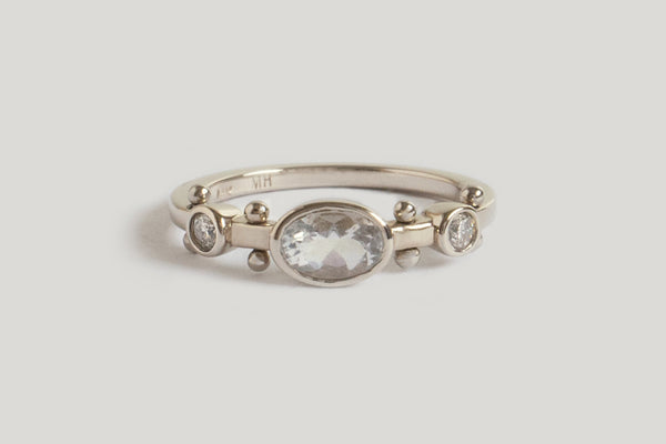 A white gold band with two small circular clear quartz settings and large oval clear quartzset in the middle. The band has a total of four sets of gold balls between each diamond setting along the sides of the band.