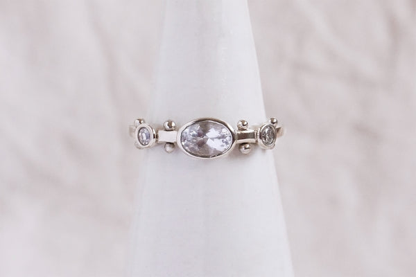 A white gold band with two small circular clear quartz settings and large oval clear quartzset in the middle. The band has a total of four sets of gold balls between each diamond setting along the sides of the band on a ring stand against a white background.