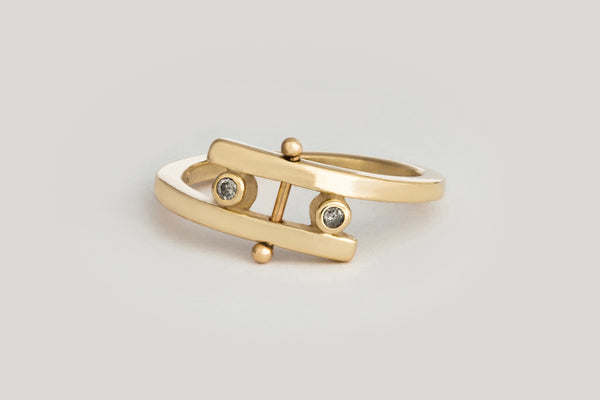 A yellow gold band that wraps around the finger and creates a gap filled with two small round grey diamond settings and a rod in the very center capped with two beads on each end.