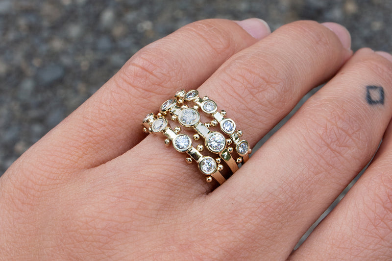 A hand modeling the 3-stone, 4-stone and 5-stone white diamond Koemi rings on the ring finger