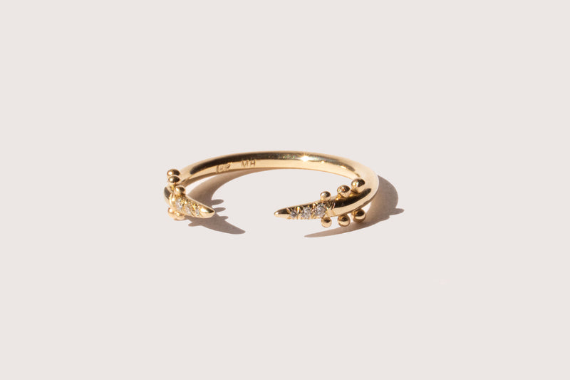 The Kuli Ring: A 14k yellow gold ring that is open in the center and has tapered ends. The ends taper to points, and there are three white diamonds set into each point. Three sets of beads sit just beyond the diamonds.