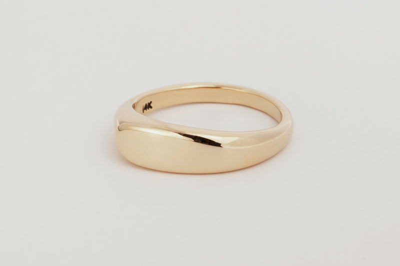 A close up of a yellow gold asymmetrical band that widens at one side and tapers at the other with softly flattened top.