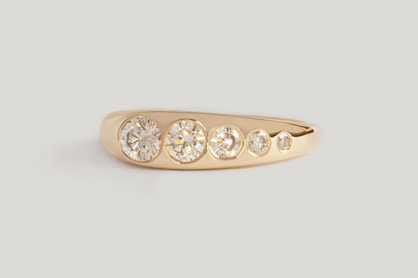 Champagne Diamond Lila Suprima Ring. Flush-set white diamond set into a tapered gold band.