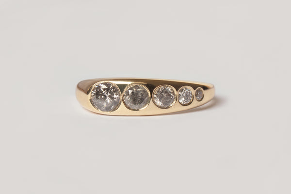 The Lila Suprima Ring: A close up front view of a yellow gold asymmetrical band featuring five sizes of flush set salt and pepper grey diamonds.