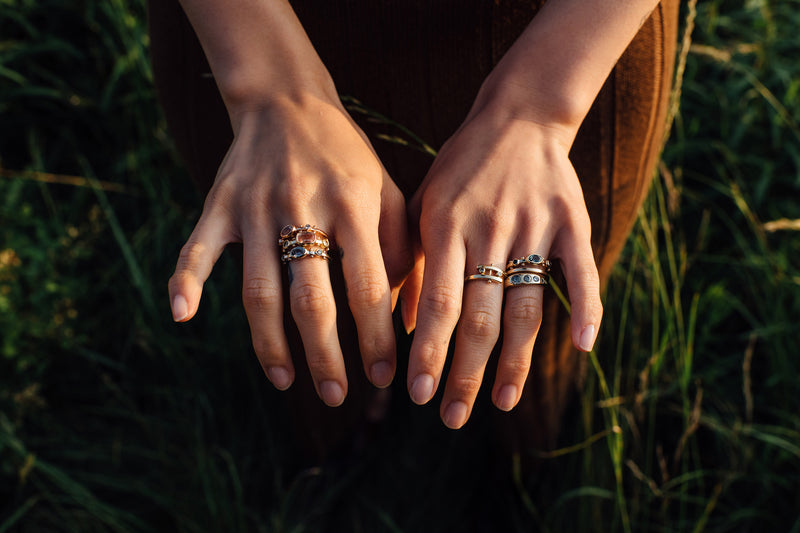 Two hands above a field of green grass with a styled stack of M.Hisae yellow gold rings light from the side by the sunlight.