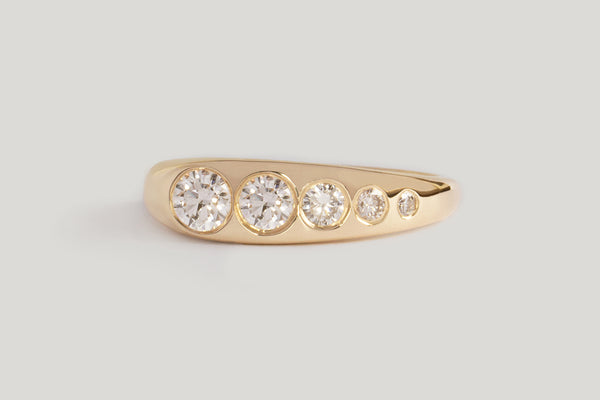 White Diamond Lila Suprima Ring. Flush-set white diamond set into a tapered gold band.