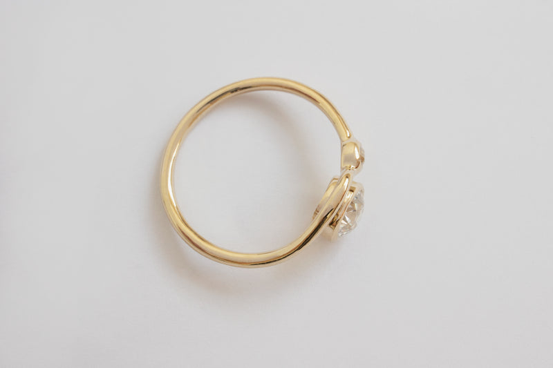 Top view of a bright white large round diamond and smaller diamond each framed in circular yellow gold setting on a wavy yellow gold band layered with another simple wavy yellow gold ring band