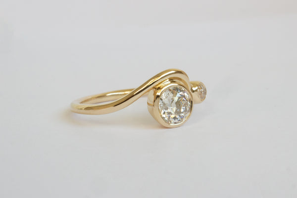 Side view of a bright white large round diamond and smaller diamond each framed in circular yellow gold setting on a wavy yellow gold band layered with another simple wavy yellow gold ring band