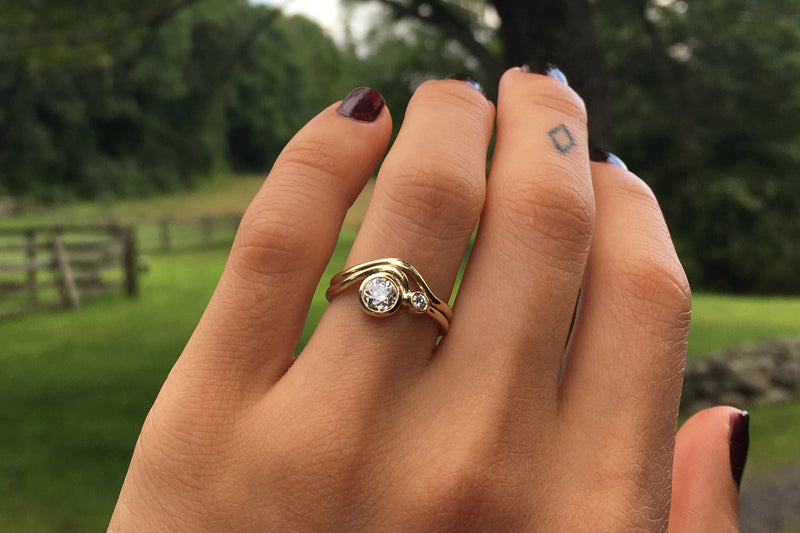 A hand wearing the Masumi and Contour ring stack with burgundy painted fingernails against a lush green forest backdrop