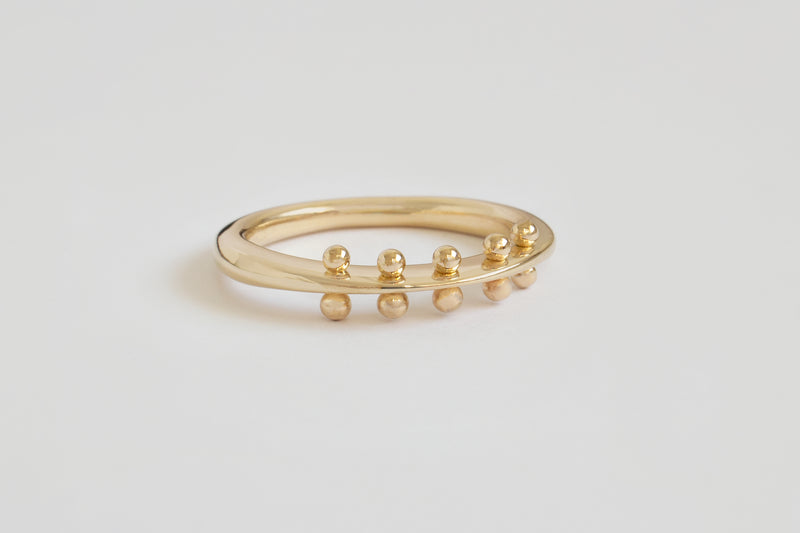 A closeup view of round yellow gold band with flattened spine featuring center spine features 5 sets of beads along the flattened spine on its side.