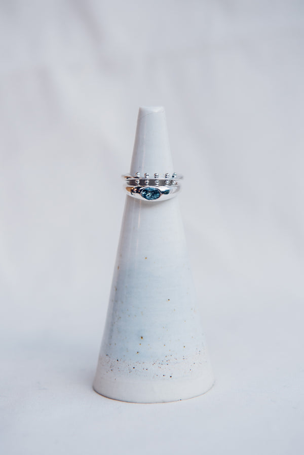 A white ring stand against a white backgroundfeaturing the sterling silver maya ring and blue montana sapphire sterling silver classic rise ring.