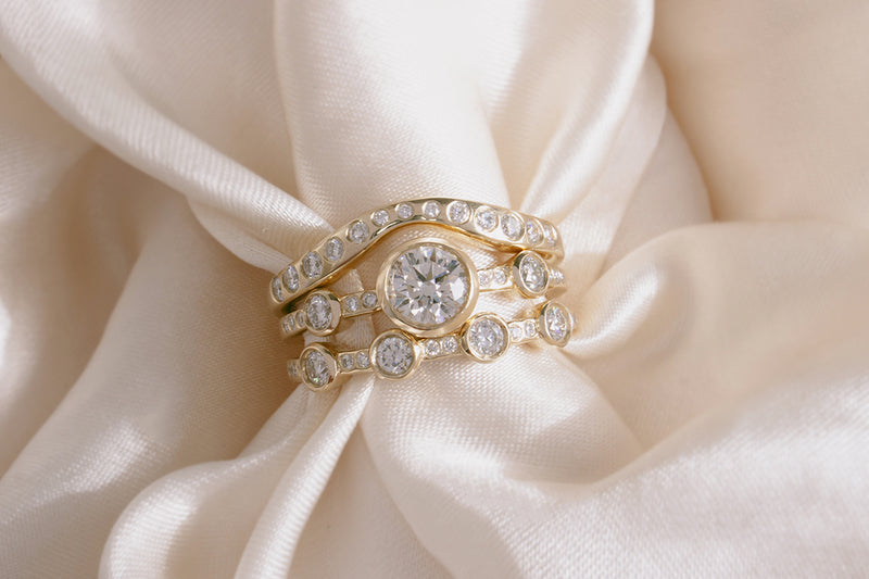 M. Hisae Crown Theia Ring, White Diamond Lana Band, and White Diamond 4-Stone Theia Ring stacked together on beautiful cream silk.