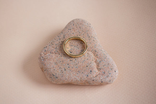 A top view of a yellow gold 3mm Nara band ontop of a speckled pink stone against a blush pink surface