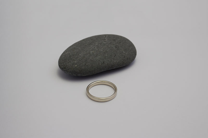 A top view of the white gold Nara band next to a dark grey stone against a light grey surface