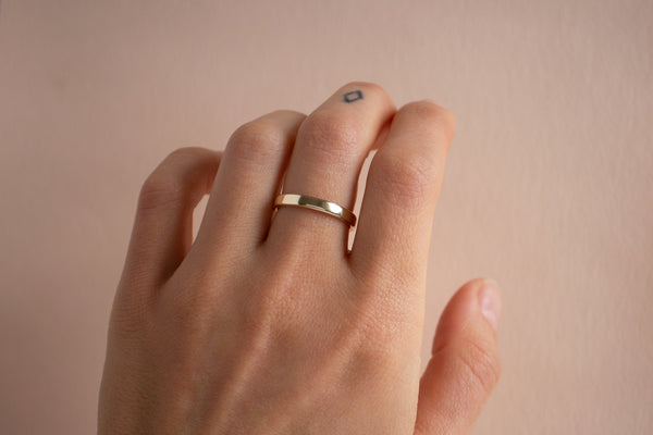 A hand wearing the 3mm white gold Nara band on the middle finger