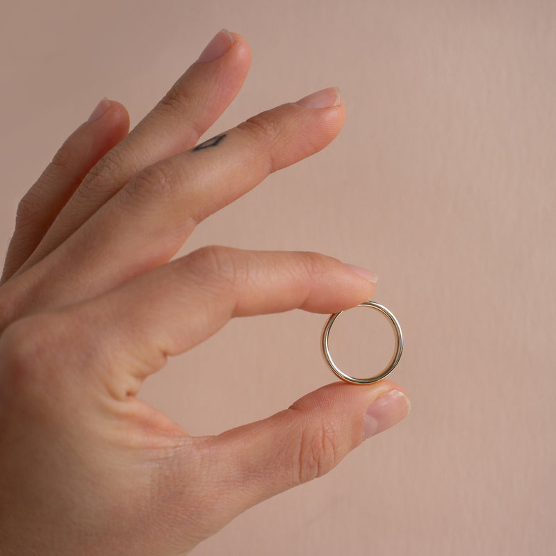 A hand holding the white gold Nara band between the thumb and pointer finger against a tan background