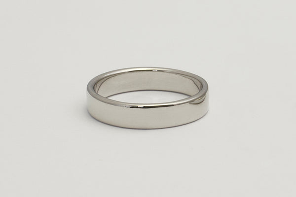 A closeup of a simple white gold wedding band with a flush flat top and bottom and slightly curved edges