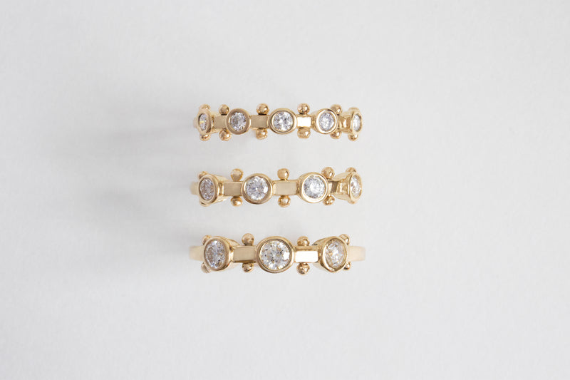 A top view of the 3-stone, 4-stone and 5-stone white diamond Koemi rings all with gold balls between each diamond setting along the sides of the band