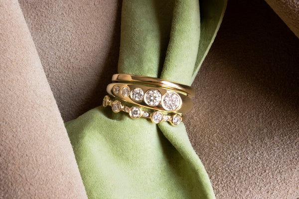 M. Hisae Ageku Band, White Diamond Lila Suprima, and 5-Stone Theia Ring stacked together on green suede.