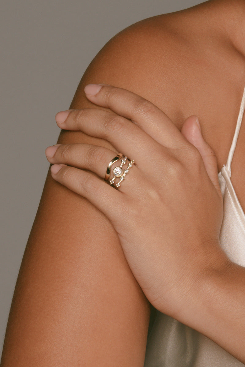 M. Hisae Crown Theia Ring, Lana Band, and White Diamond 5-Stone Theia Ring on a model's hand.