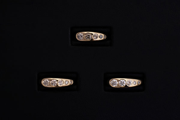 Three Lila Suprima Rings. Flush-set diamonds in a tapered gold band.